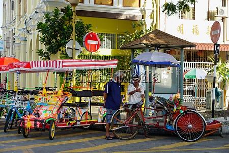 two trishaw driver read newspaper at