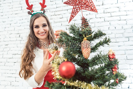 woman with deer horns decorating christmas