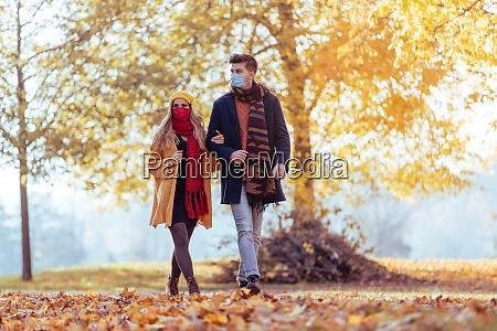 couple wearing mask walking in autumn