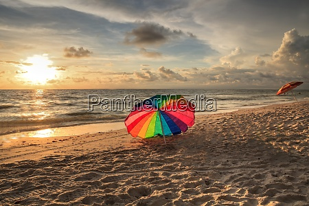 rainbow umbrella on white sand at