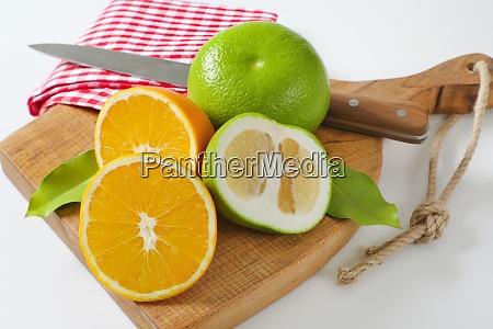 green grapefruits and halved orange