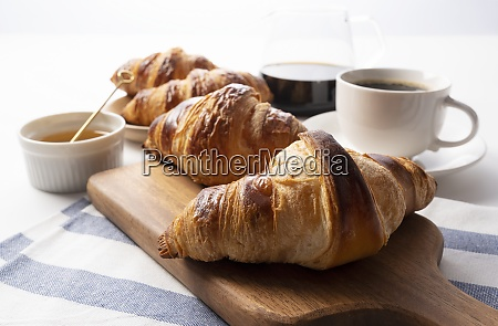 a croissant and coffee and honey