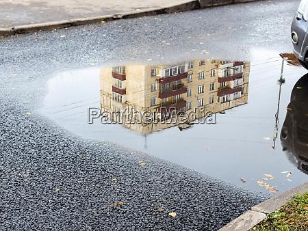puddle with reflection of municipal urban