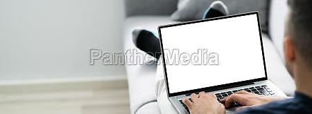guy sitting on sofa using laptop