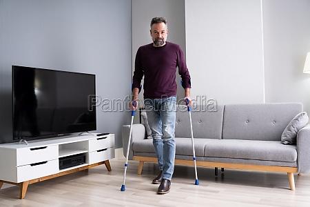 elderly man using crutches to walk