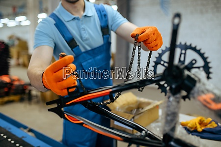 bicycle factory worker holds bike chain
