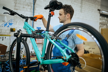 bicycle factory worker holds mountain bike