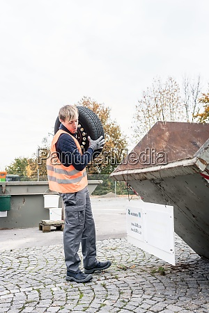 man putting old tire in container