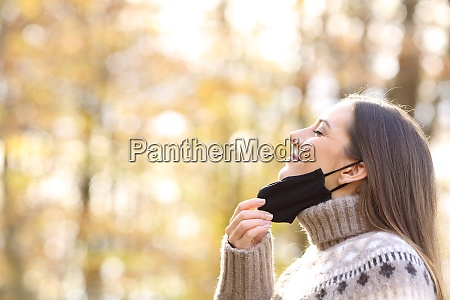 woman relieving taking off mask to
