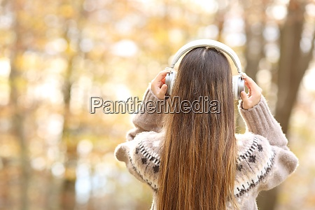 back view of woman putting headphones