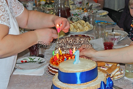 mother decorating festive cake with candle