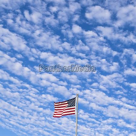 american flag against cloudy sky