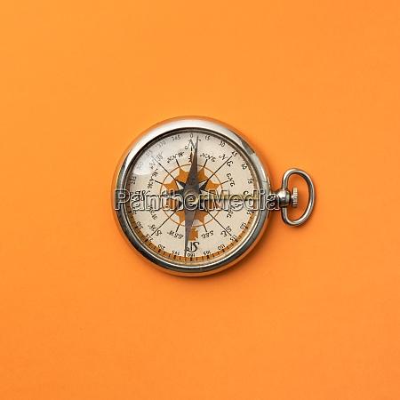 antique compass on orange background