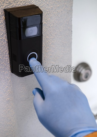 hand with surgical on door bell