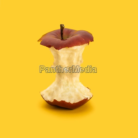 core of red apple against yellow