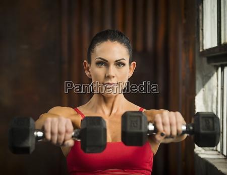 sporty woman lifting dumbbells