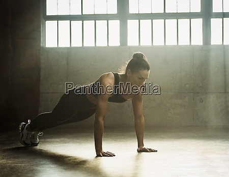 woman exercising in warehouse