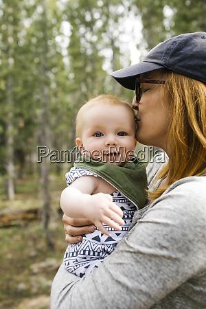 woman kissing baby son 6 11