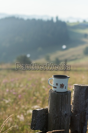 metal mug in nature with mountains