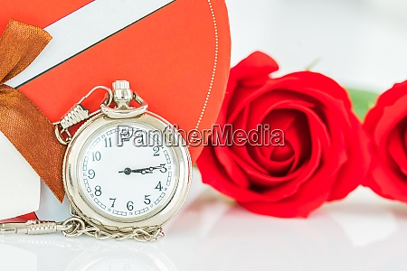 close up pocket watch and red