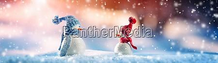 little knitted snowmen on soft snow