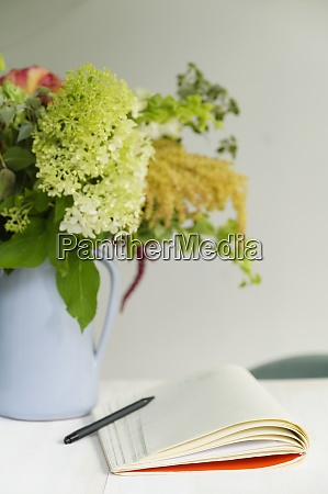 notepad and flower bouquet on table