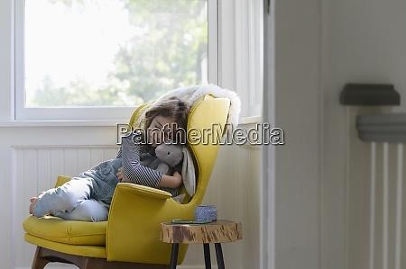 girl 5 7 relaxing in armchair
