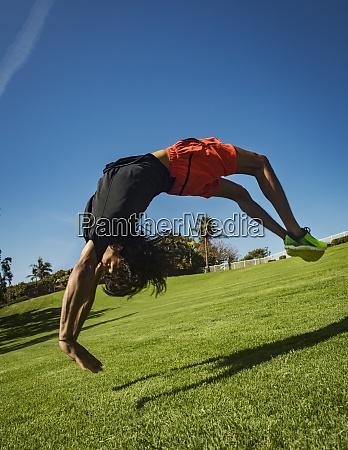 man flipping over grass