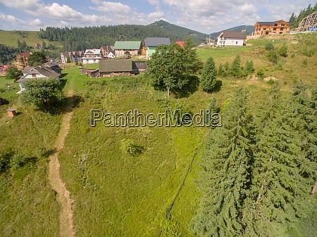 village near deep green mountaines aerial