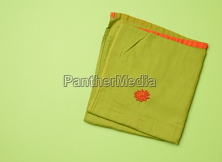 folded green napkin green background
