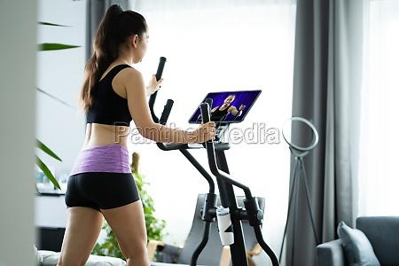 woman training on elliptical trainer online