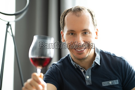 man drinking wine in video conference