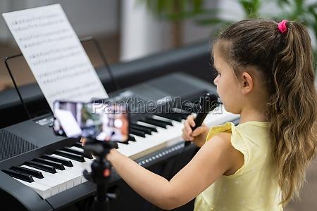 child girl playing music keyboard piano