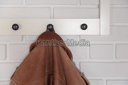 brown leather jacket hanged on white