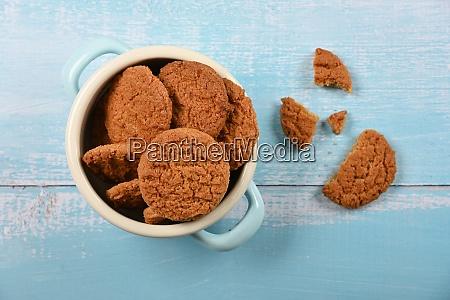oatmeal cookies in pannikin on blue