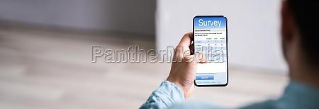 man filling online survey form