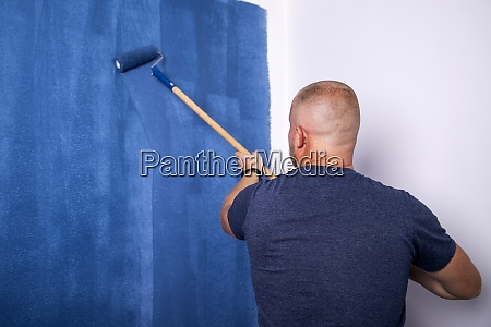 young man painting the white wall