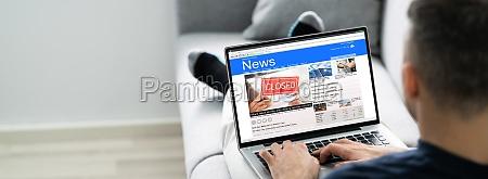 man using computer reading electronic news
