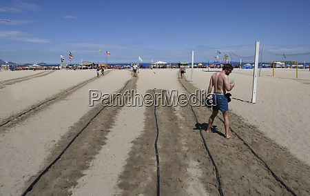 watering hot sand on paths at