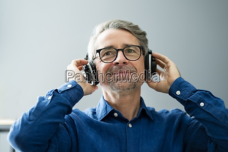 smiling older senior listening music