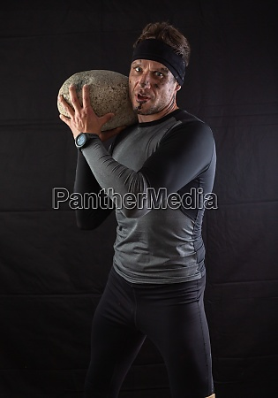 sporty man holding a large heavy