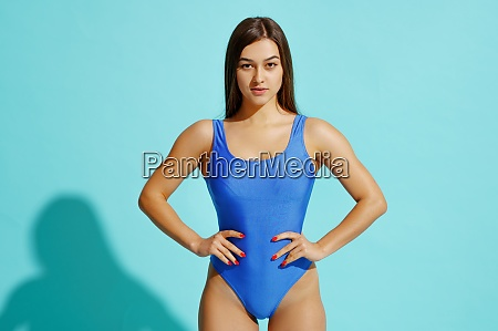 sportive woman in swimsuit poses in