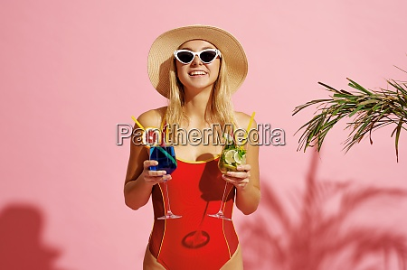 woman in swimsuit poses with coctails