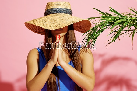 woman in swimsuit and hat poses
