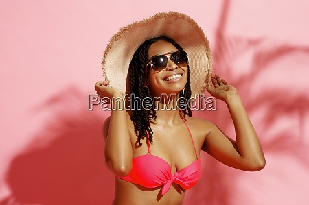 young tanned woman in swimsuit hat