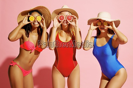 women in swimsuits and hats poses