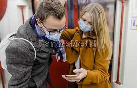 people using phone in train wearing