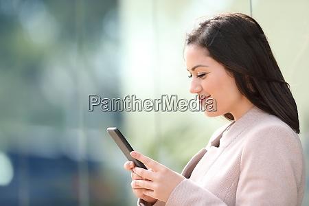 busineswoman reading text on smart phone
