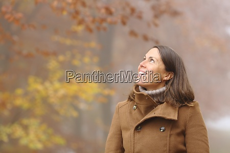 happy middle age woman contemplating in