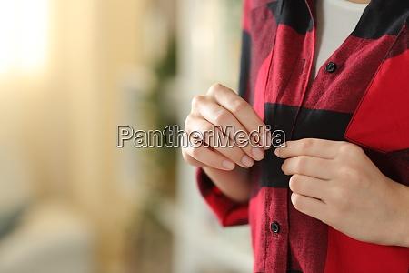 teen hand dressing fastening button of
